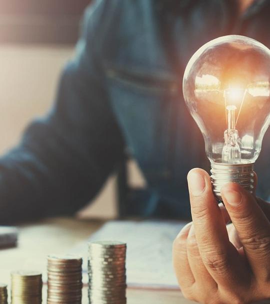 Man sieht eine Glühbirne und gestapelte Münzen - symbolisierend  für Ersparnis